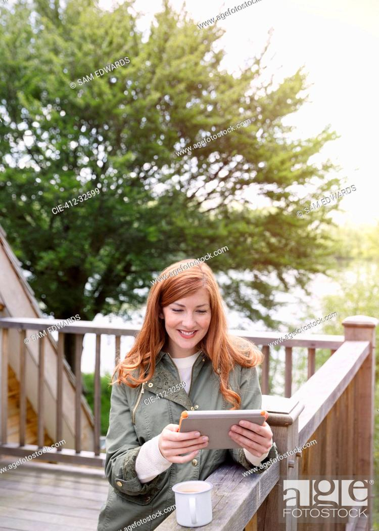Stock Photo: Smiling woman with red hair using digital tablet on cabin balcony.