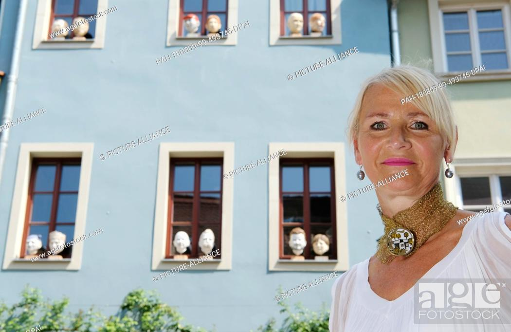 Stock Photo: 08 August 2018, Germany, Naumburg: Heike Minner stands in front of her house in downtown Naumburg, with her sculptures placed in the windows.