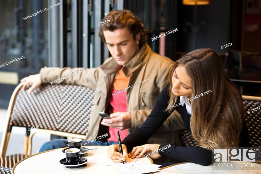 Stock Photo: Young couple in street cafe woman writing postcard, man using mobile phone.