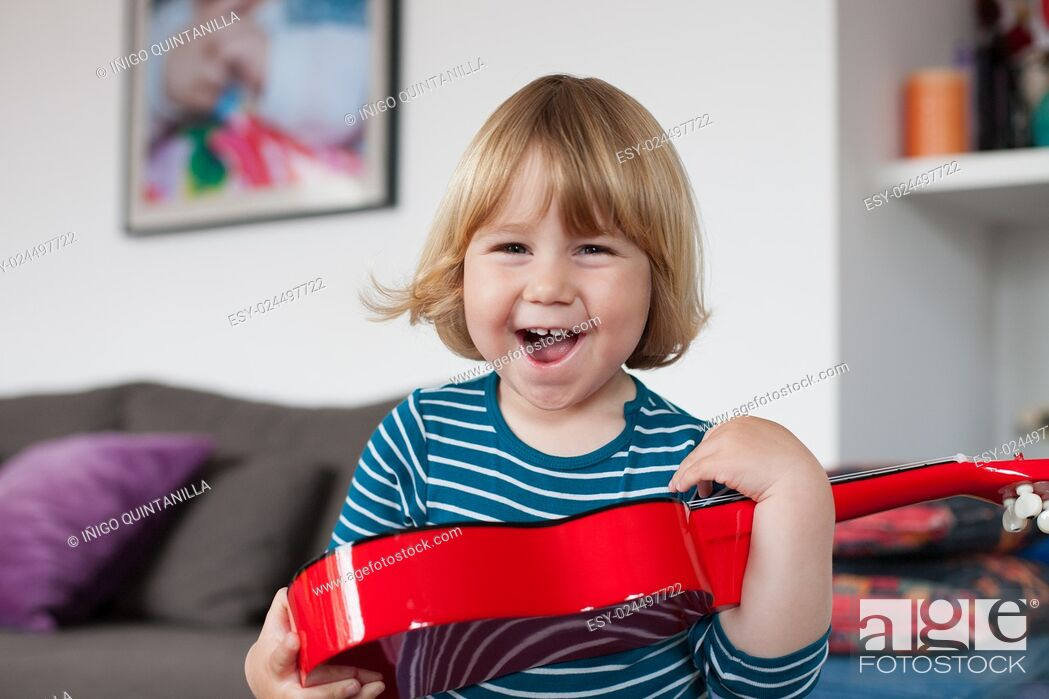 Stock Photo: blonde two years old child with striped blue and white sweater inside home with red spanish little guitar in her hands laughing happy looking at camera.