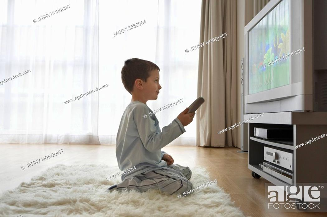 Stock Photo: Boy 7-9 sitting on floor watching cartoons in television.