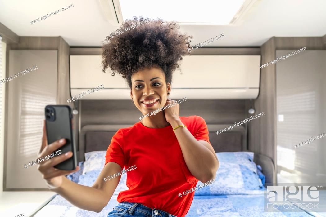 Stock Photo: beautiful African woman taking a photo from her smartphone.