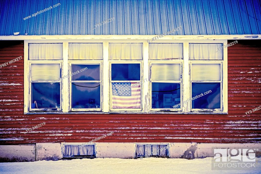 Stock Photo: American flag hanging in the window of an old abandoned school house in the UP of Michigan.