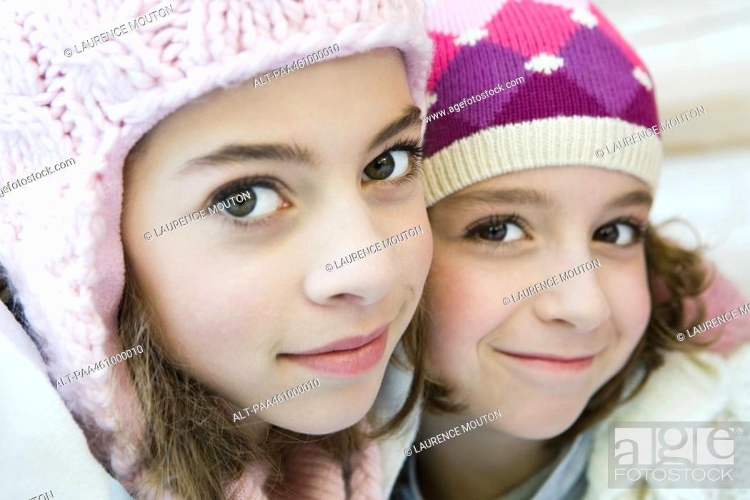 Stock Photo: Two young sisters smiling at camera, both wearing knit hats, cheek to cheek, portrait.