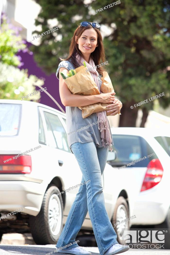 Stock Photo: Beautiful young woman crossing a road with paper bags full of vegetables.
