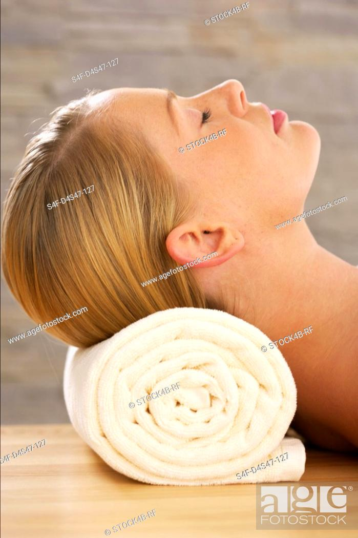Stock Photo: Young woman with closed eyes lying on a towel roll.
