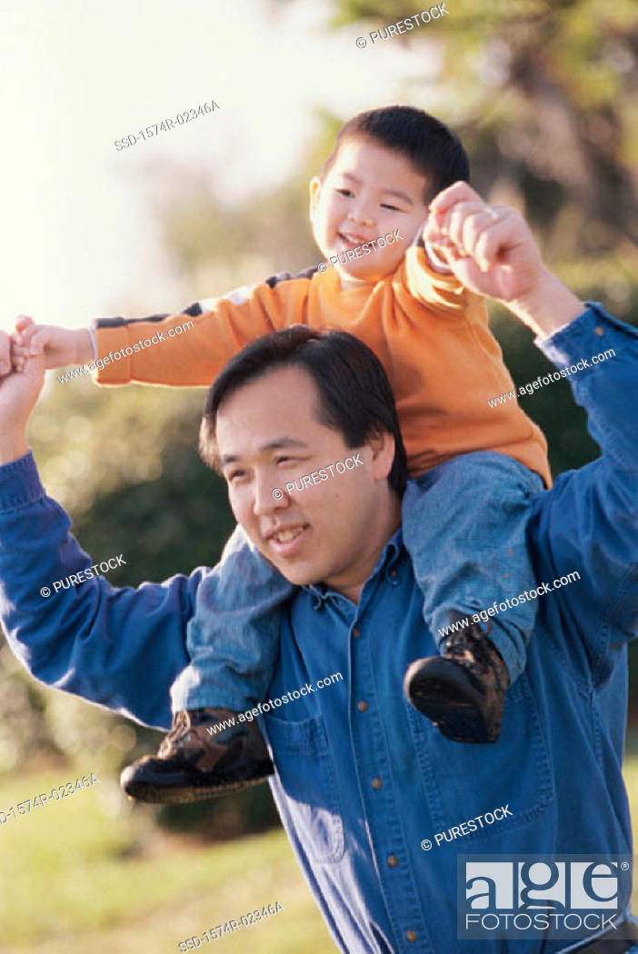 Stock Photo: Father carrying his son on his shoulders.