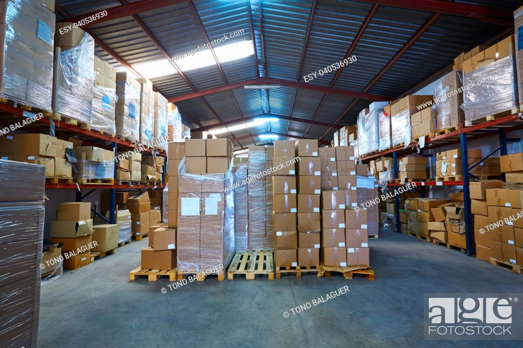 Stock Photo: Warehouse stograge with stacked boxes in rows of a printing factory.
