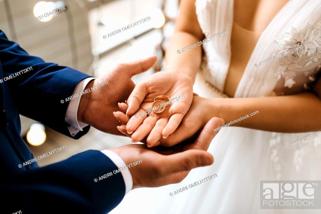 Imagen: groom puts bride on wedding ring.