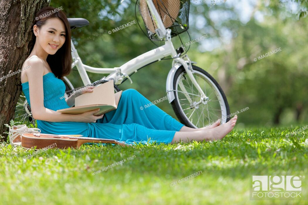 Imagen: Young woman sitting on the lawn and holding a book with smile,.