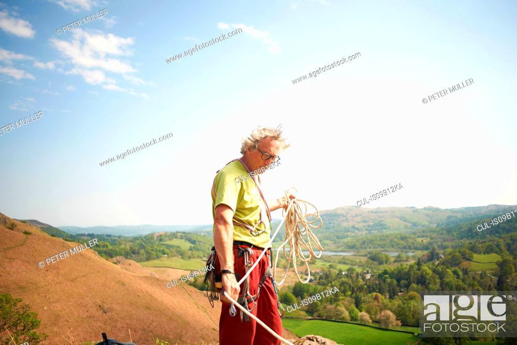 Stock Photo: Rock climber on hillside preparing climbing rope.