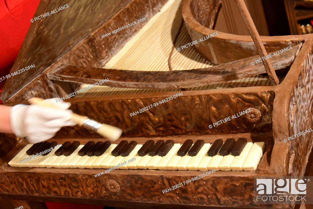 Stock Photo: 14 February 2020, Saxony-Anhalt, Halle (Saale): Dust on a harpsichord made of solid and dark chocolate is removed by head chocolatier Claudia Schulz-Heimann.