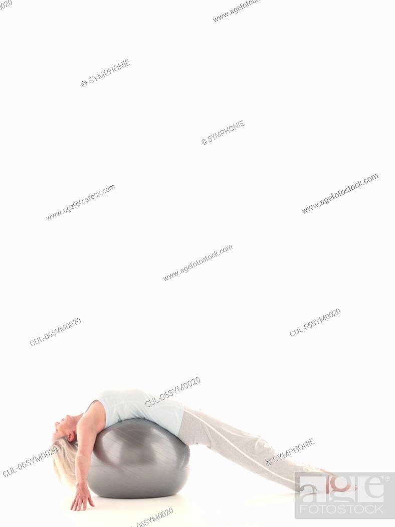 Stock Photo: Mature woman lying on exercise ball.