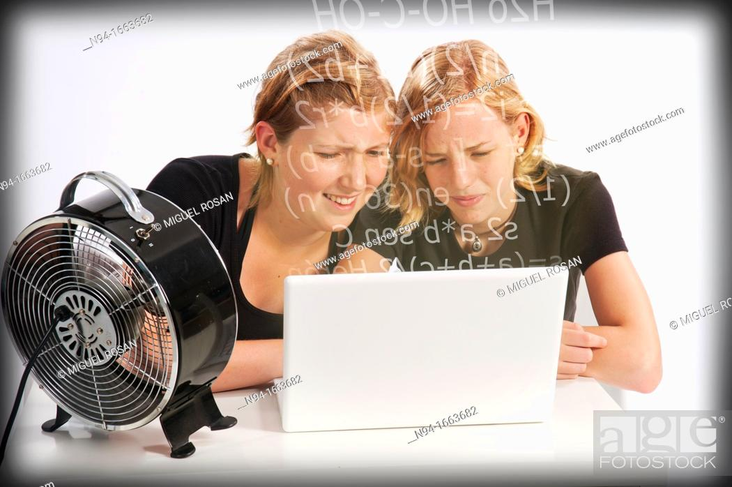 Stock Photo: Two teenage girls studying mathematics in front of the laptop.