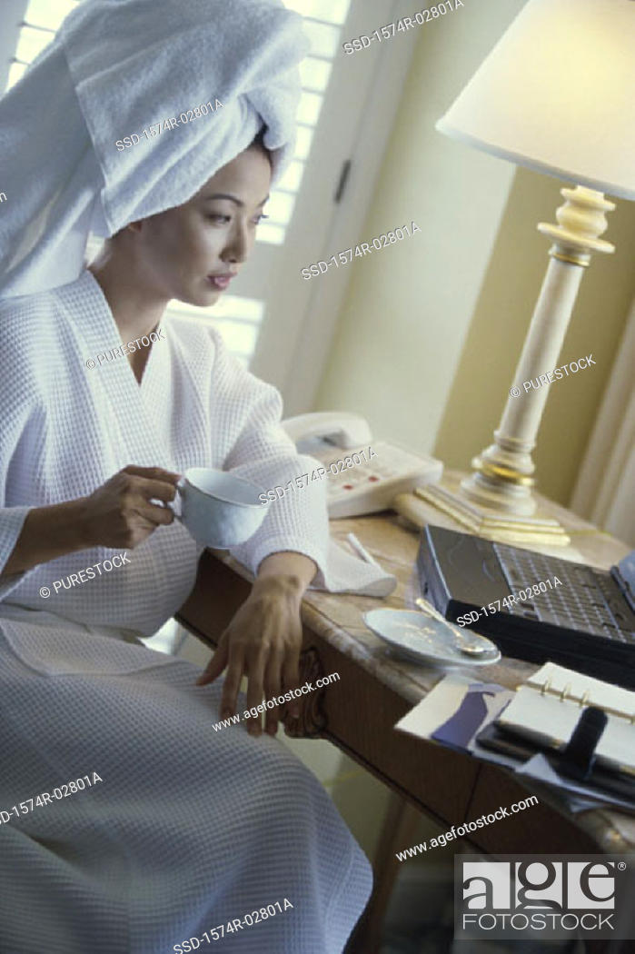 Stock Photo: Young woman wearing a bathrobe holding a cup of coffee and looking at a laptop in a hotel room.