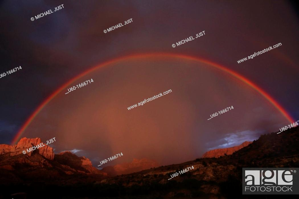 Stock Photo: A full rainbow stretches across the sky during a lightning and thunderstorm at Zion National Park, Utah.