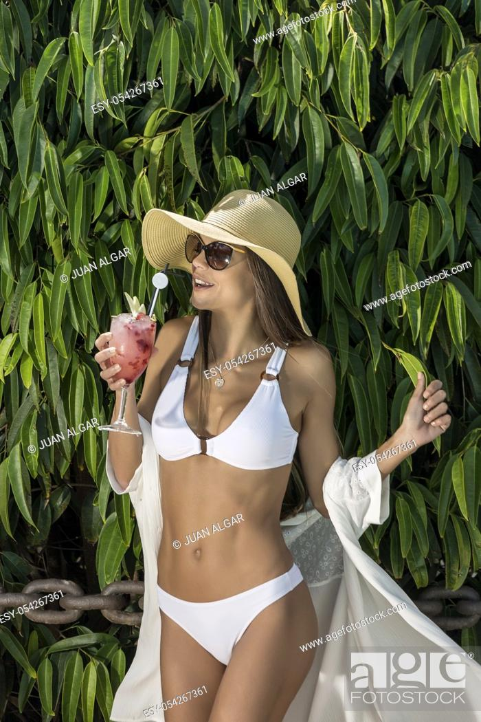 Stock Photo: Young slim brunette in white bikini and hat enjoying delicious sweet cocktail standing against green tropical tree.