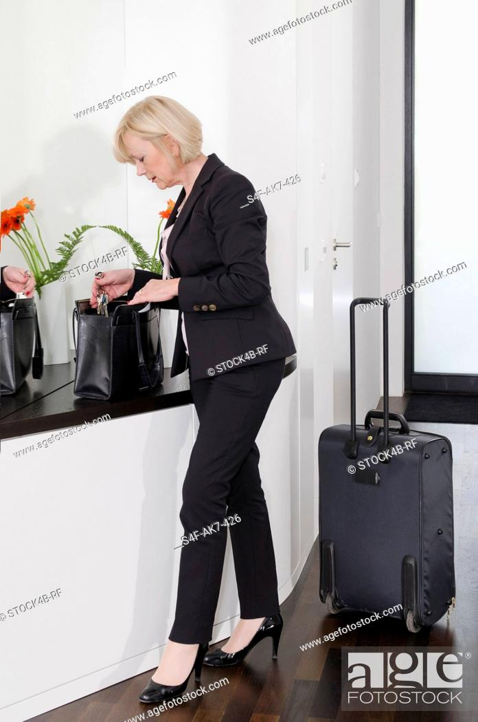 Stock Photo: Elegant woman with baggage holding keyring.