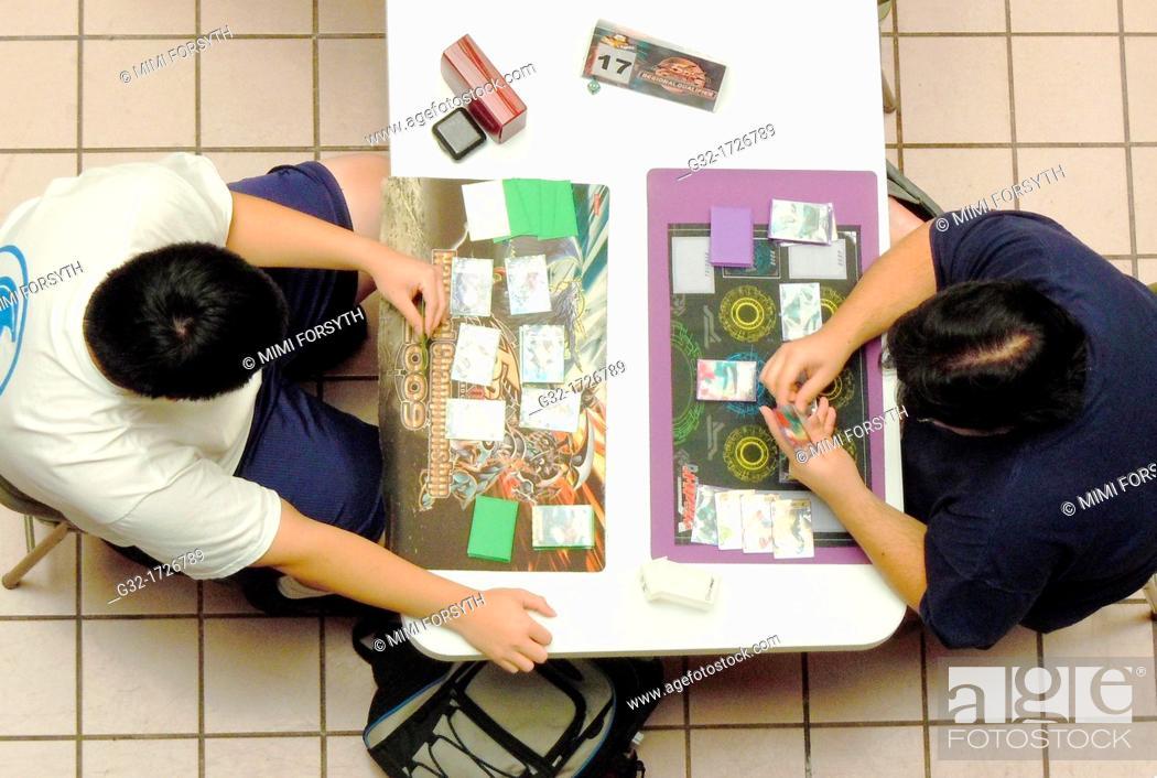 Stock Photo: two teens play Vanguard Cardfight tournament.