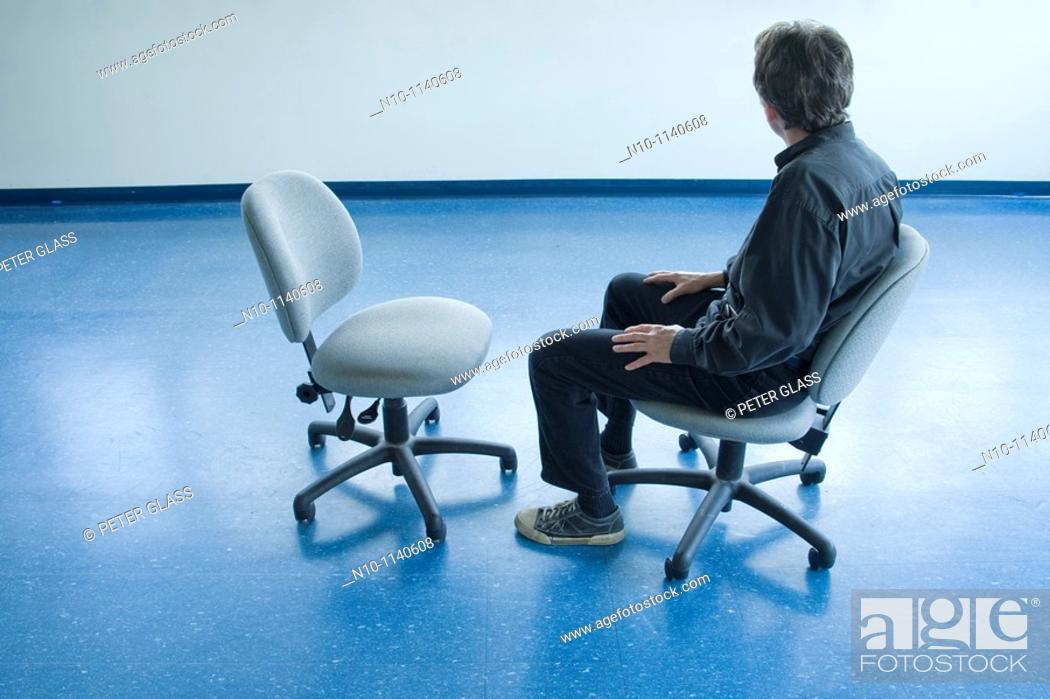 Stock Photo: Man sitting on a chair in an empty office.