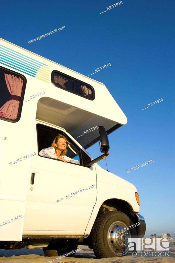 Stock Photo: Mature woman looking out window of motor home, low angle view.