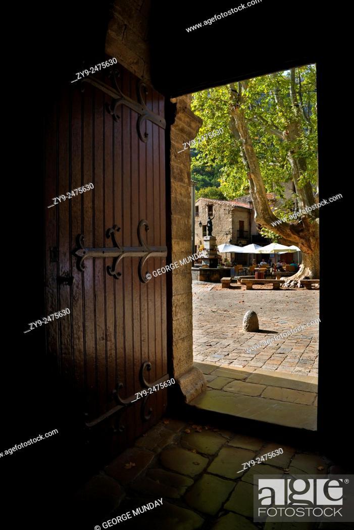 Stock Photo: The village square seen through the abbey doorway, St Guilhem le Desert, Languedoc-Roussillon, France.