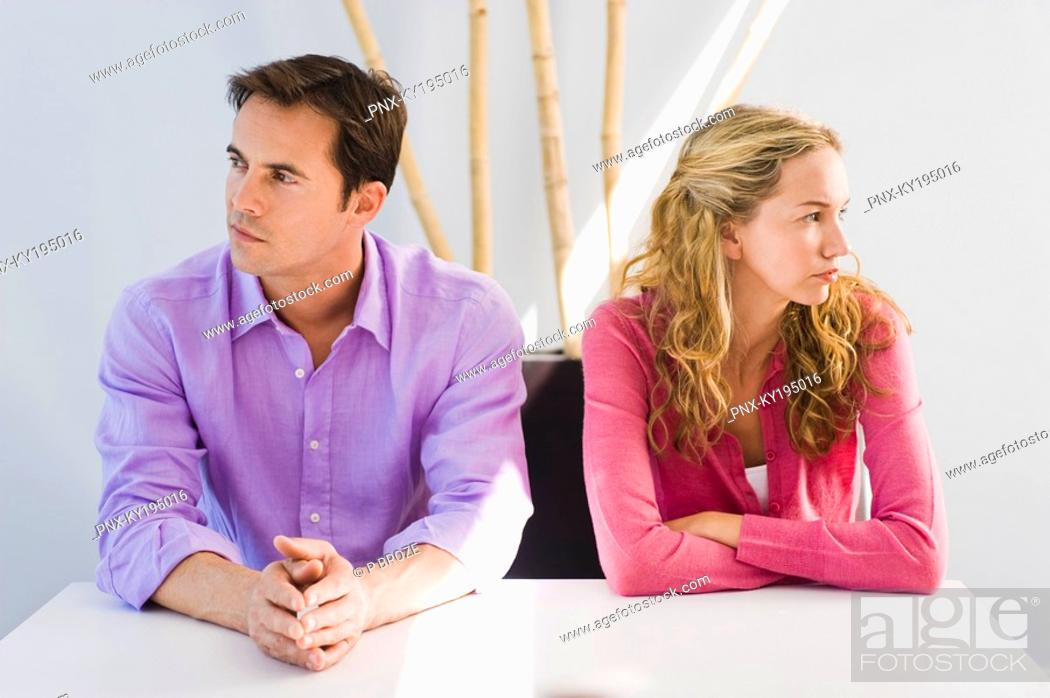 Stock Photo: Couple sitting side by side and ignoring each other.