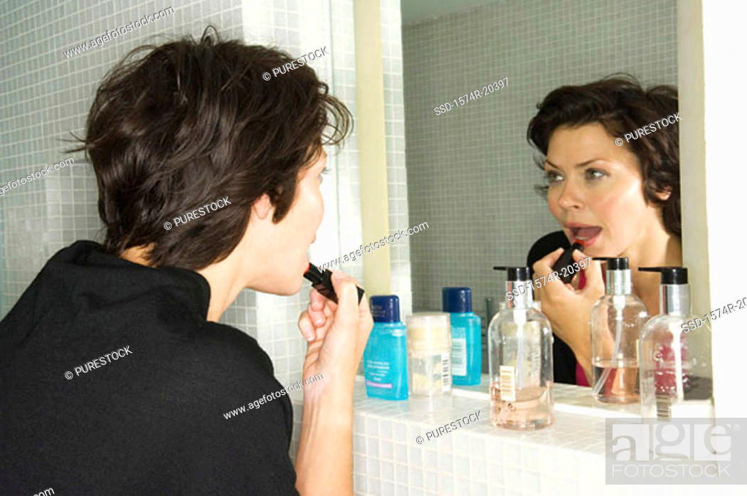 Stock Photo: Side profile of a young woman applying lipstick to her lips.