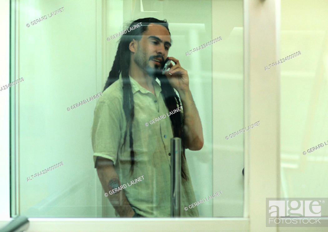 Stock Photo: Man on cell phone, view through glass.