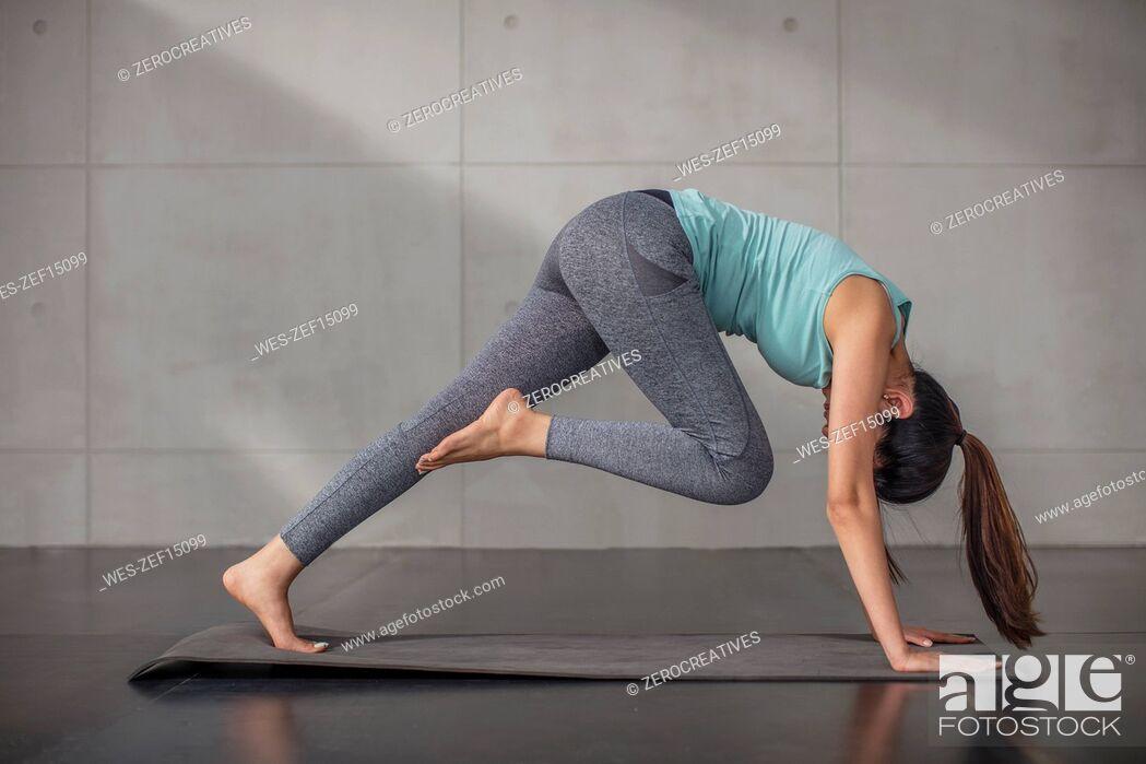 Stock Photo: Young woman doing yoga exercise in studio.
