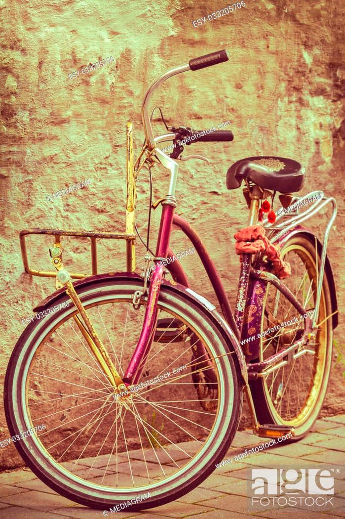 Stock Photo: Retro styled image of a colorful bike against an old wall.