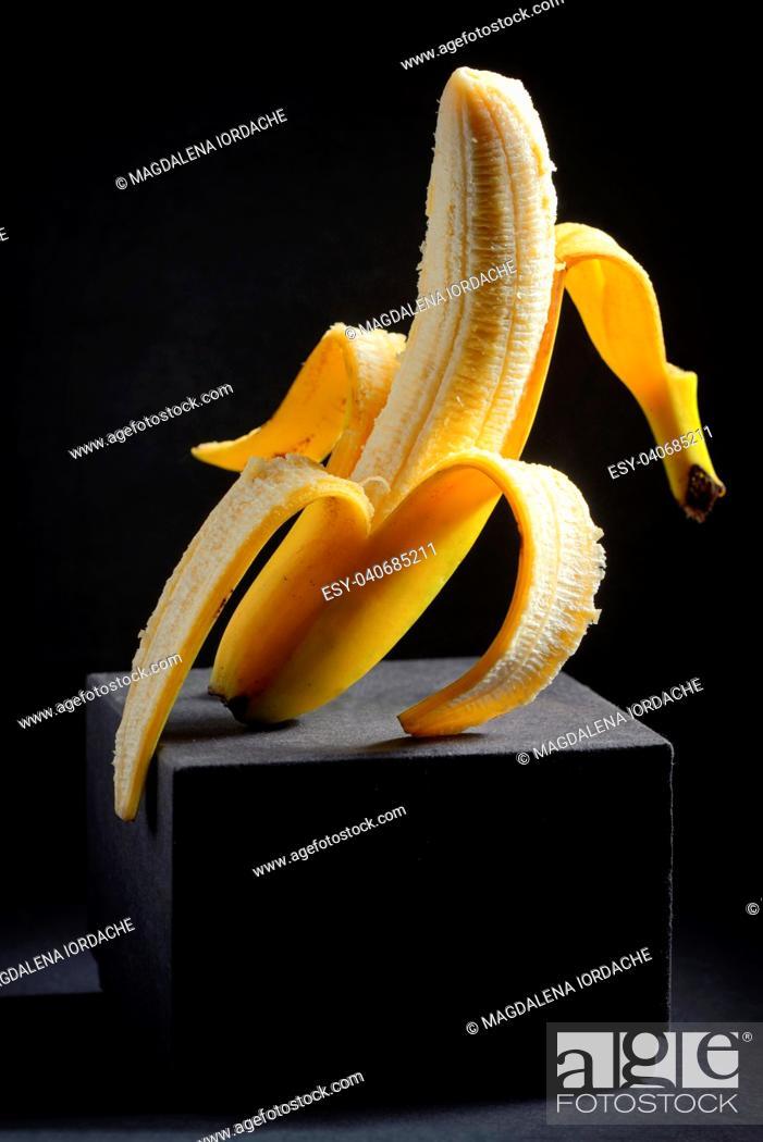Imagen: Vertical peeled banana on black background.