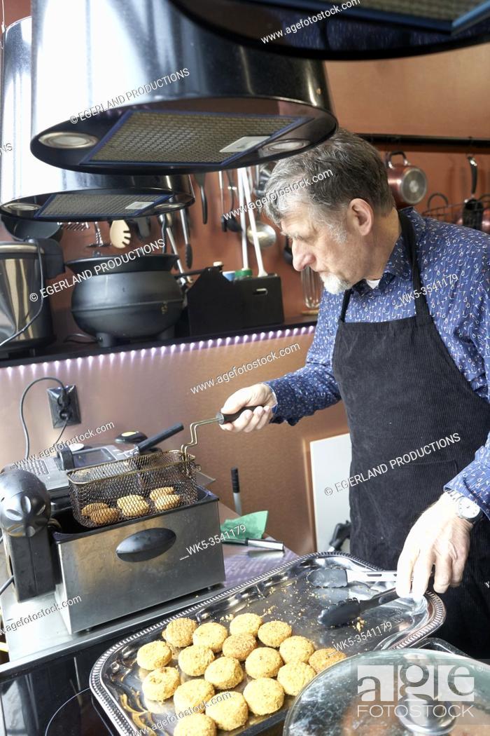Stock Photo: man deep-frying Falafel.