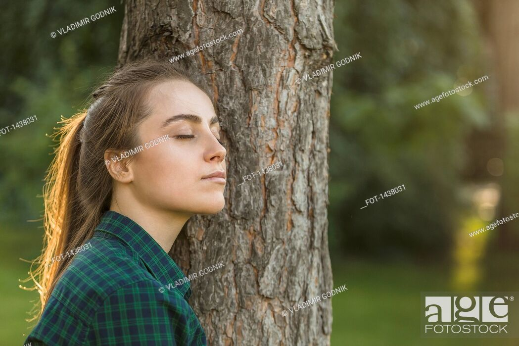Stock Photo: Beautiful woman with eyes closed leaning on tree trunk at park.