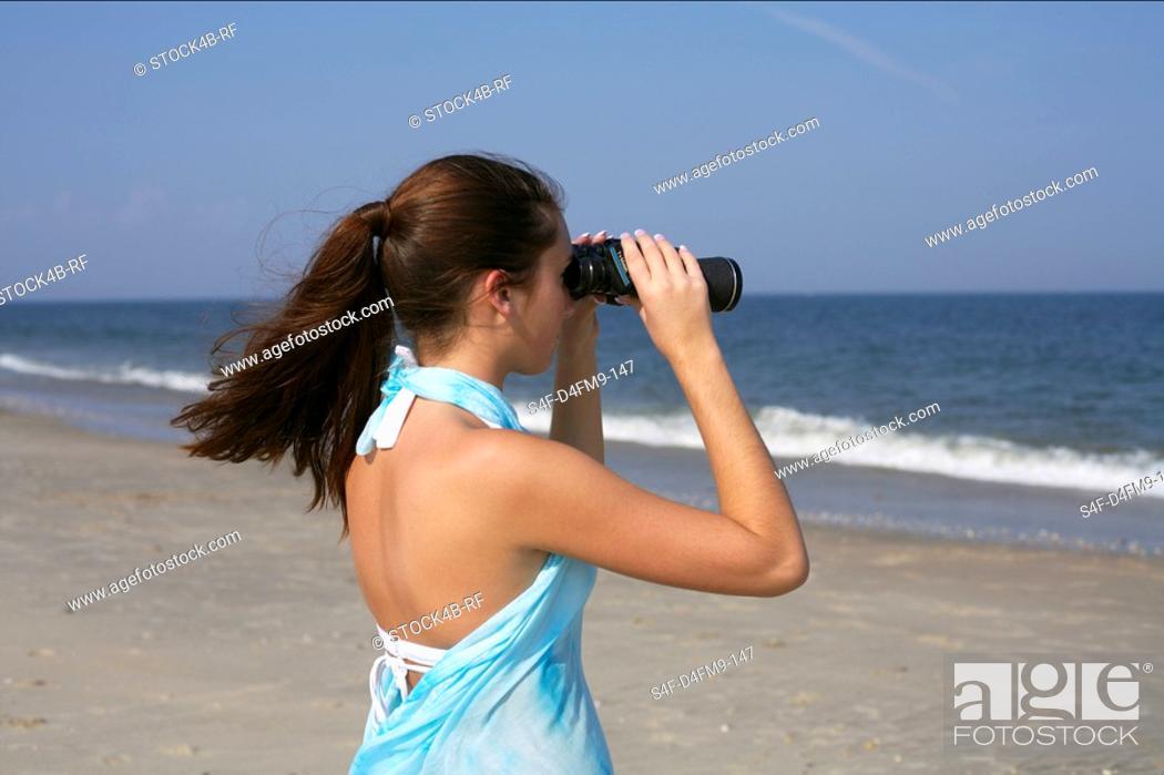 Stock Photo: Young brunette woman looking through binoculars, selective focus.