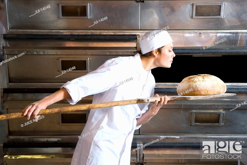 Stock Photo: Female baker taking bread from oven, side view.
