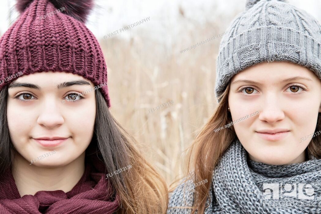Stock Photo: Two teenage girls wearing knit hats and scarves and looking at the camera; Scarborough, Ontario, Canada.