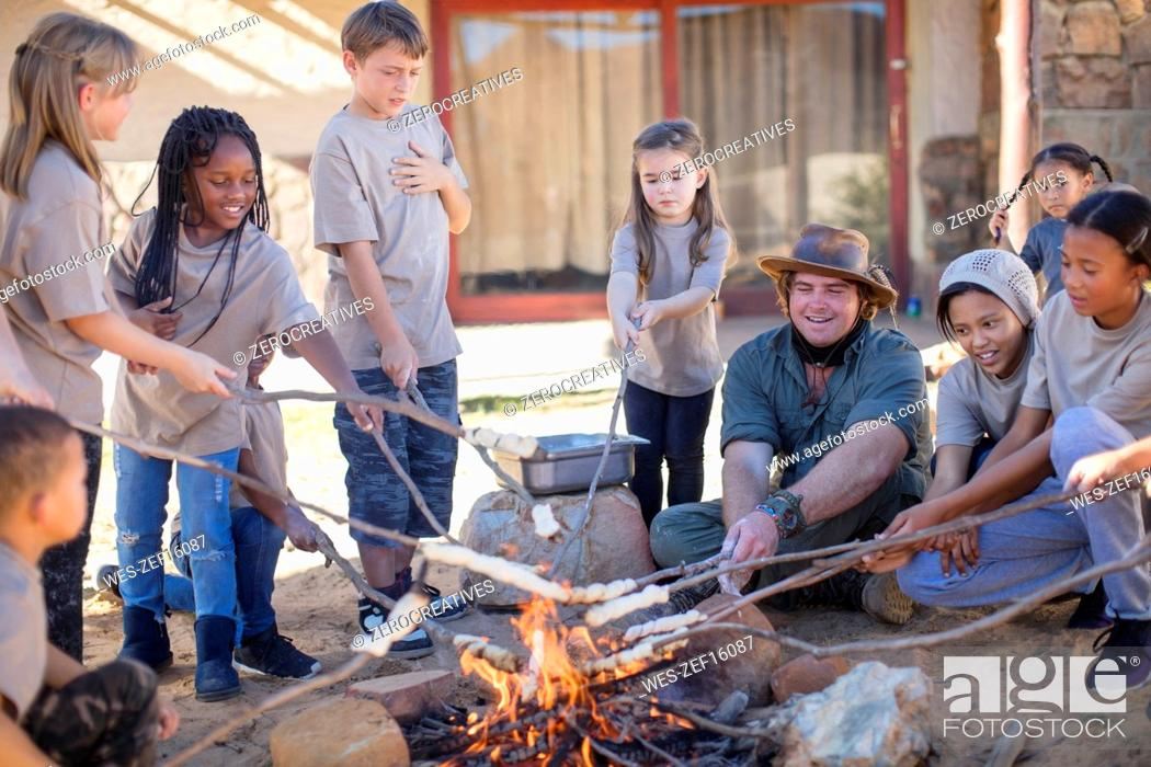 Imagen: Children and guide roasting twist bread at camp fire.