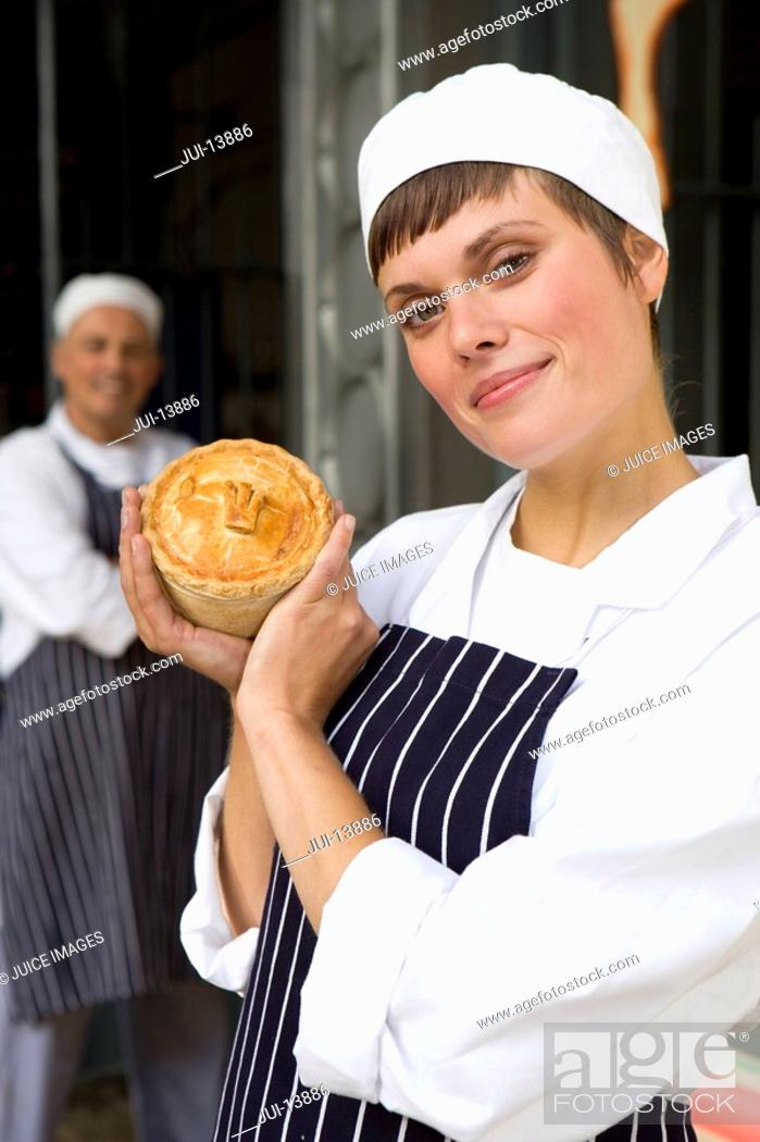 Stock Photo: Female baker with pie by colleague, smiling, portrait.