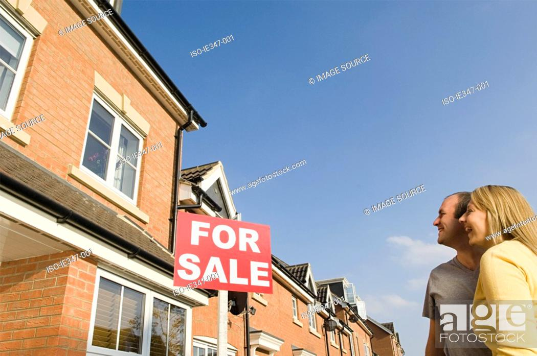 Stock Photo: Couple looking at house for sale.