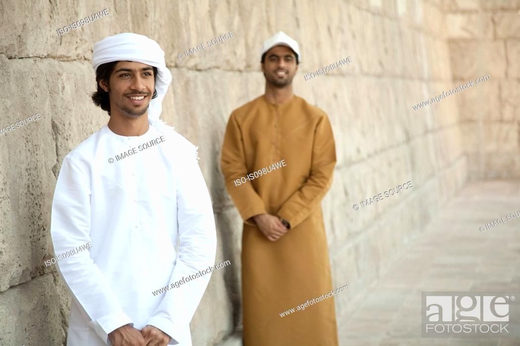 Stock Photo: Middle Eastern men looking at by stone wall.