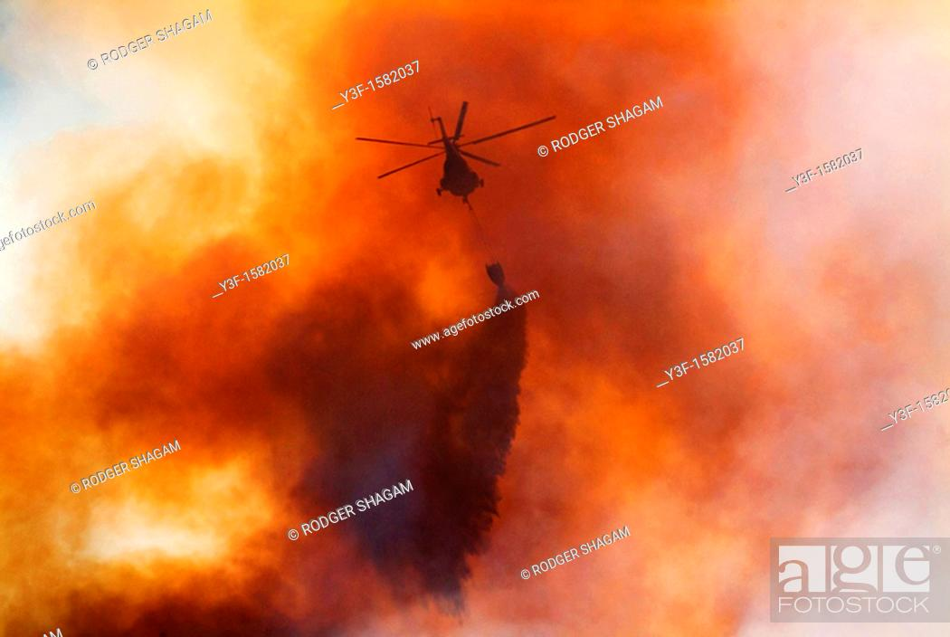 Stock Photo: A helicopter drops water on a mountain fire  Table Mountain, Cape Town, South Africa.