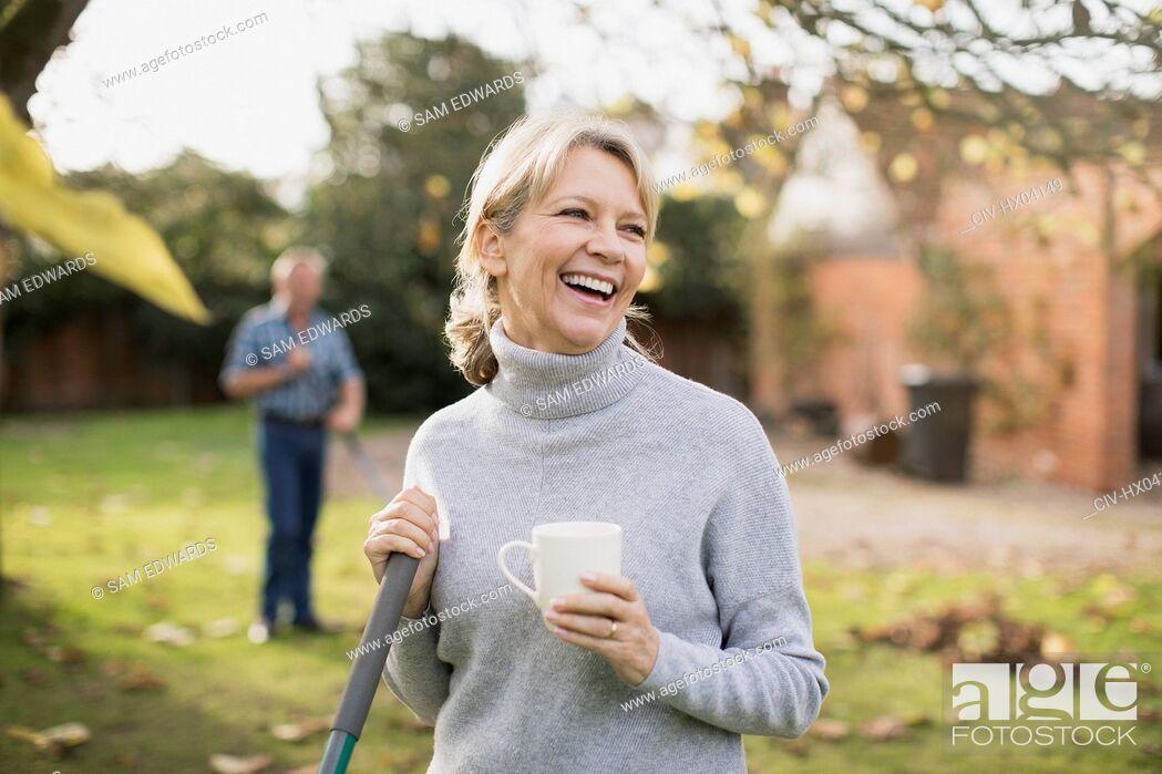 Stock Photo: Happy mature woman drinking coffee and raking autumn leaves in backyard.