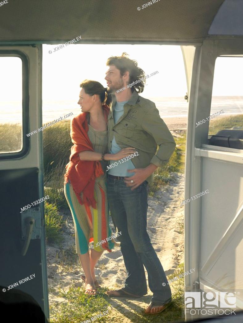 Stock Photo: Young couple embracing view through open door of camper van.