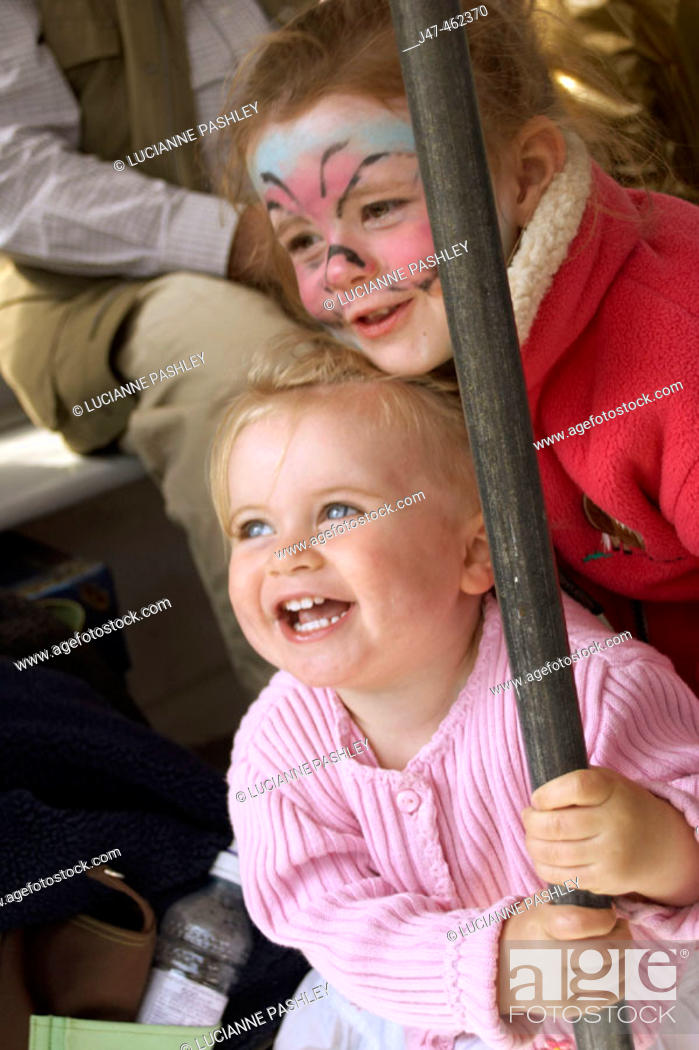 Stock Photo: 3 year old girl and 18 month old baby girl, swing round a pole,laughing.