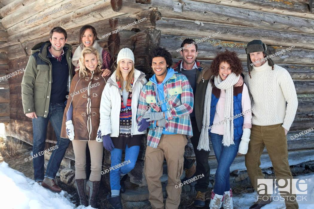Stock Photo: Portrait of smiling friends leaning on cabin wall.