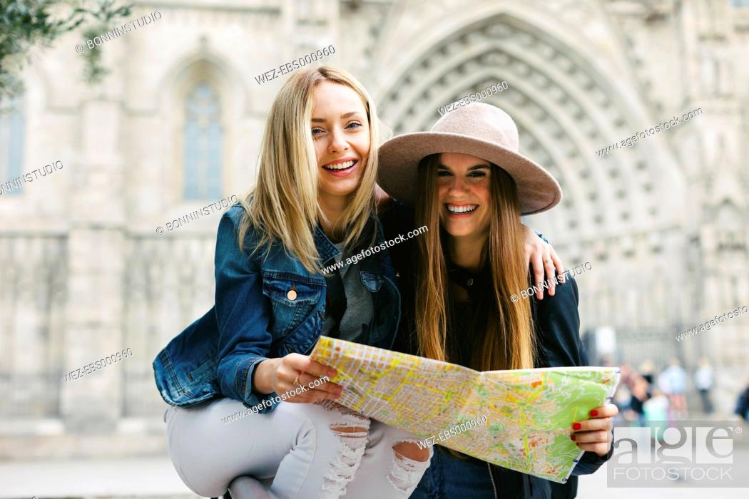 Imagen: Spain, Barcelona, two happy young women reading map.