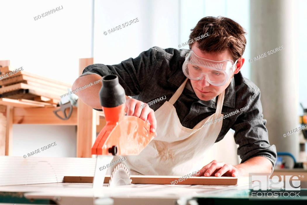 Stock Photo: Carpenter using saw in workshop.