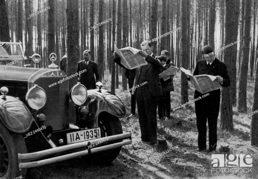 Stock Photo: A break in the woods, 1936. Nazi leader Adolf Hitler (1889-1945) and colleagues reading the papers while they take a break during a car journey.