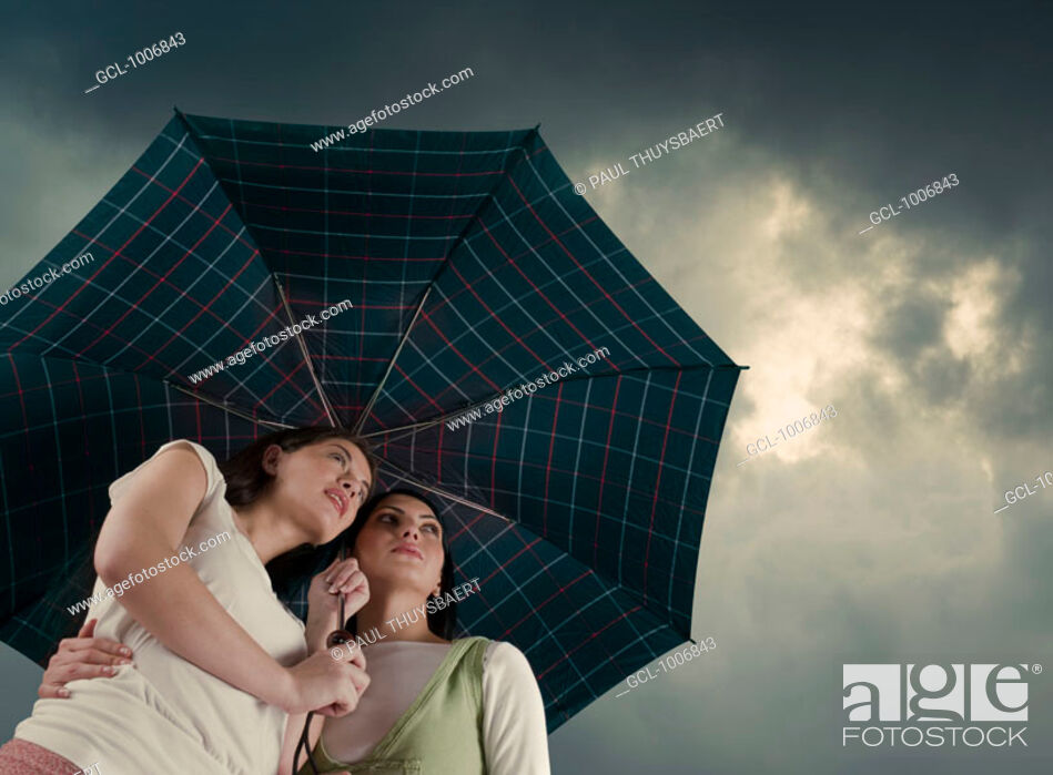 Stock Photo: Two women under an umbrella.